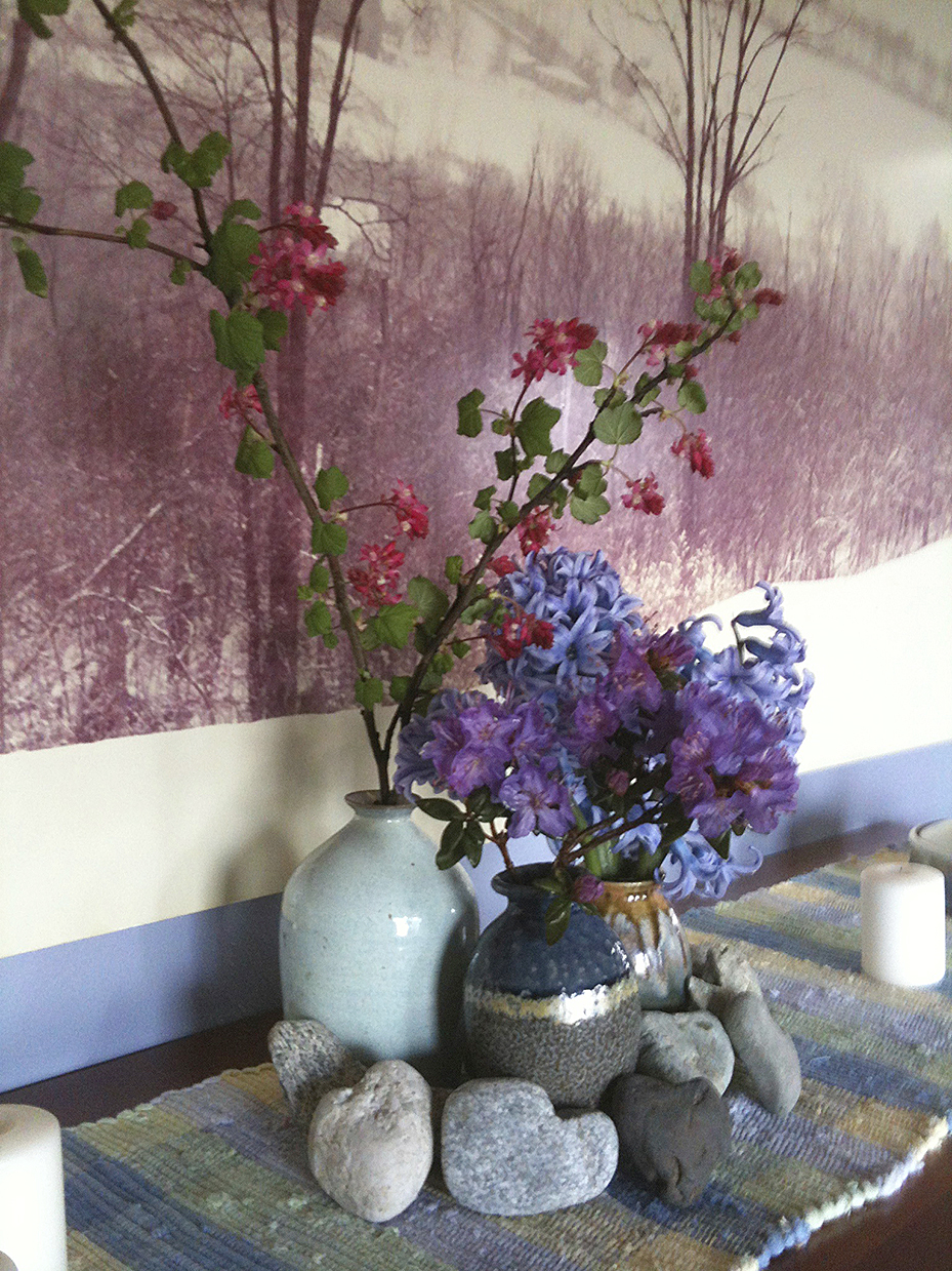 spring flowers in pottery vases with stone hearts