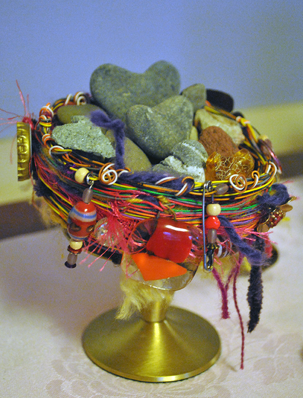 Stone hearts in a colorful wire nest